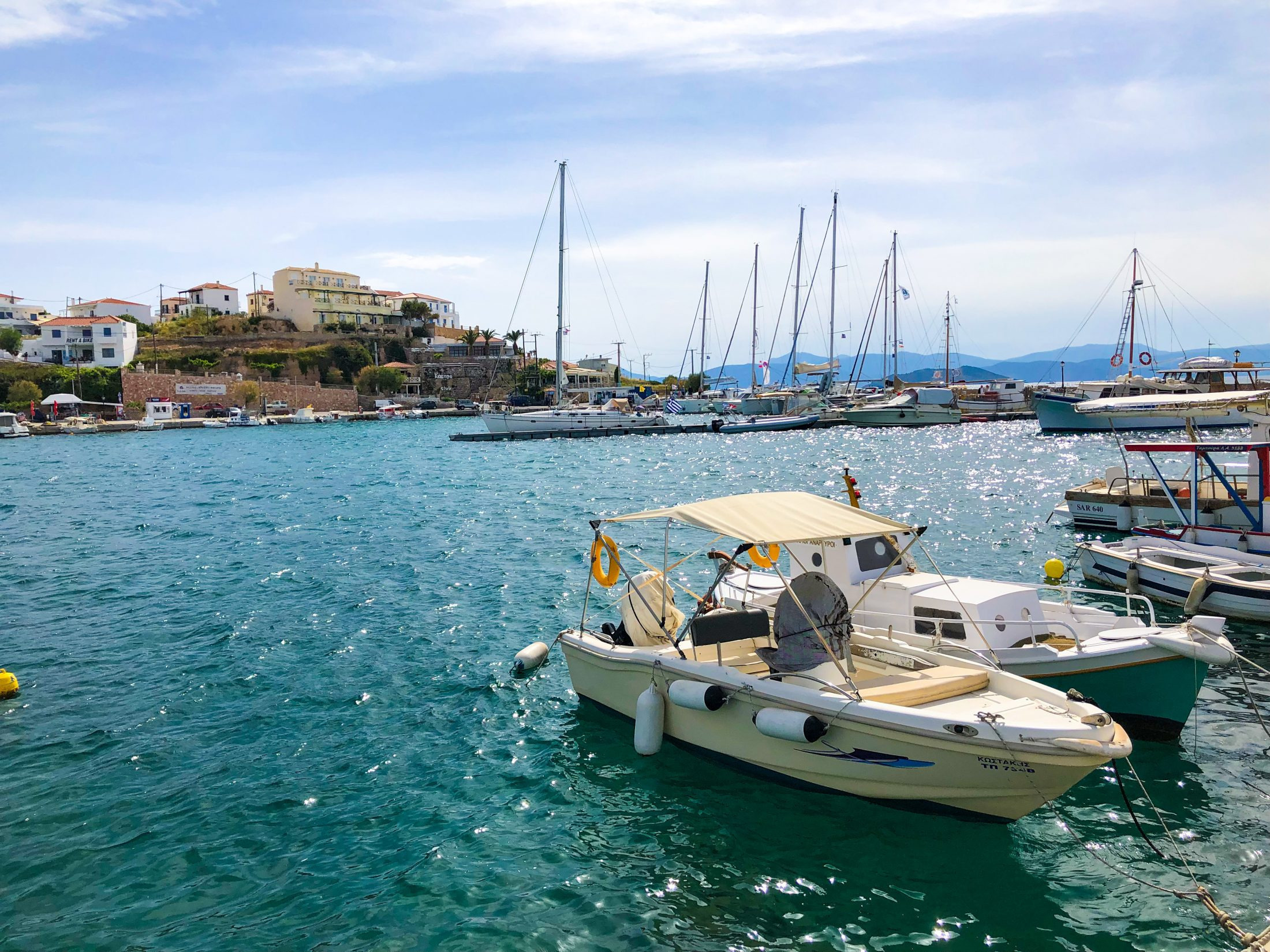 Many motor and sailing boats are in the port of Megalochori